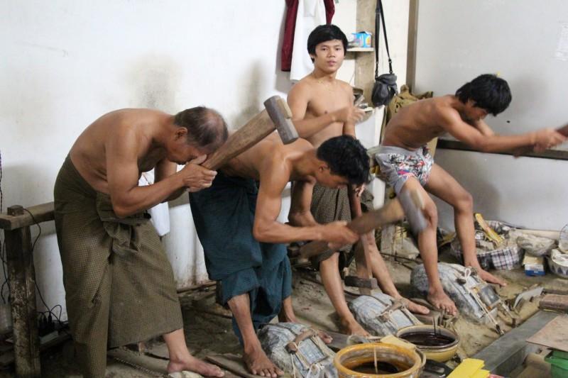 Die Männer pressen von Hand die hauchdünnen Gold-Plättlis, die auf Buddha-Statuen aufgetragen werden können.