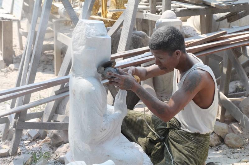 Ein Mann beim Schleifen einer Buddha-Statue