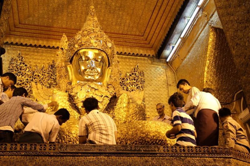 Gold-Plättlis werden auf die Buddha-Statue angepresst.
